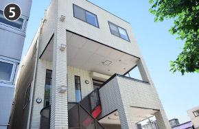 玄関入口は赤い階段を上った2階